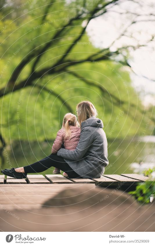 Mother sits with child on a jetty on the shore of a lake Child girl Nature natural Family Parents Infancy Cute Love Safety (feeling of) tranquillity