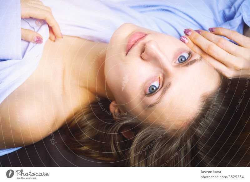 Closeup of young beautiful woman in blue lying in bed. Natural beauty. Selective focus. Film style romantic relaxation spa face body health treatment selective