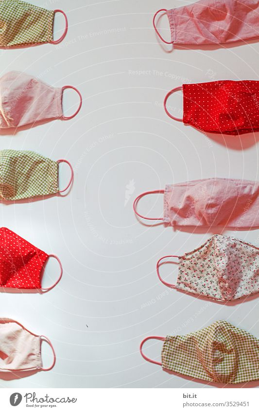 Many, colorful, self-sewn masks, as a mouthguard, protective mask, protection against infection with corona, disease, viruses as well as smog and air pollution, lie on a white background.