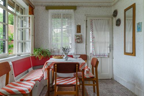 Tidy Dining room interior of an old traditional Hungarian folk house interiors socialism furniture rural countryside pattern wallpaper white red green nature