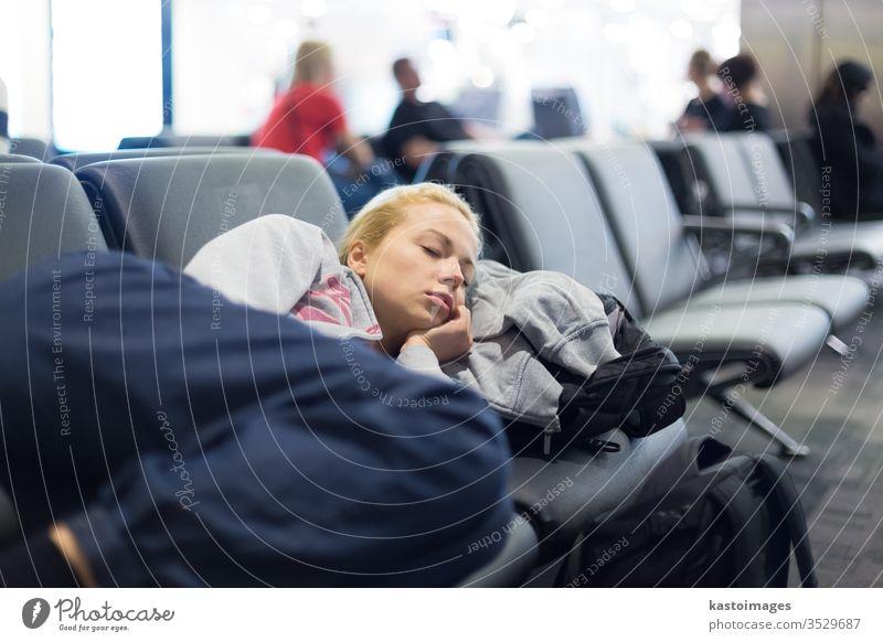 Tired female traveler sleeping on airport. woman rest nap wait station delay patience luggage train baggage flight tourist gates immigration railway platform