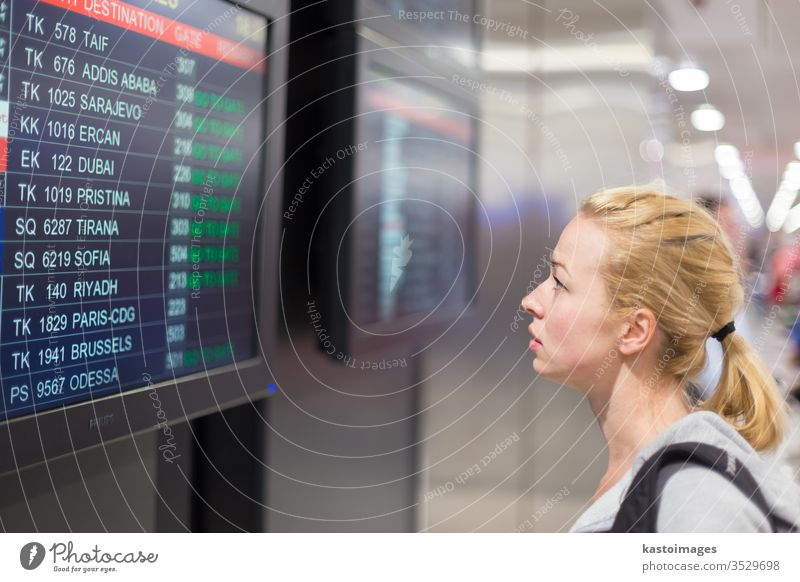 Passenger looking at flight information board. airport timetable display travel schedule woman young destination departure tourist baggage traveler girl luggage