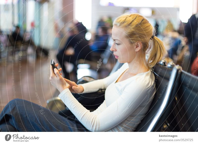 Female traveler using cell phone while waiting. woman station passenger luggage transport airport destination young network sitting bench casual female tourist