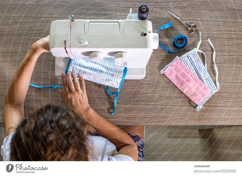 Woman making face masks with a sewing machine at home 2019-ncov above close-up cloth clothes clothing combat corona corona virus coronavirus cotton covid
