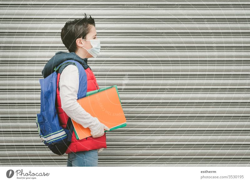 covid-19,kid with medical mask and backpack who walks to school coronavirus child epidemic student pandemic quarantine back to school city schoolboy health