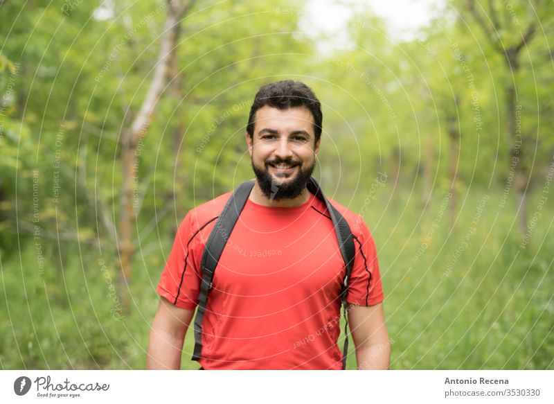 Attractive bearded man walks through the woods hiking with his backpack hike forest outdoors happy nature walking arab middle eastern tree one man only 30s 40s