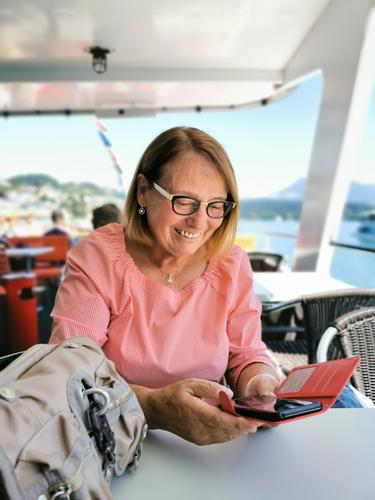 Ü70 Woman checking joyful messages on her smartphone during a cruise Senior citizen joyfully retired pensioner Navigation ship Boating trip Laughter Mode