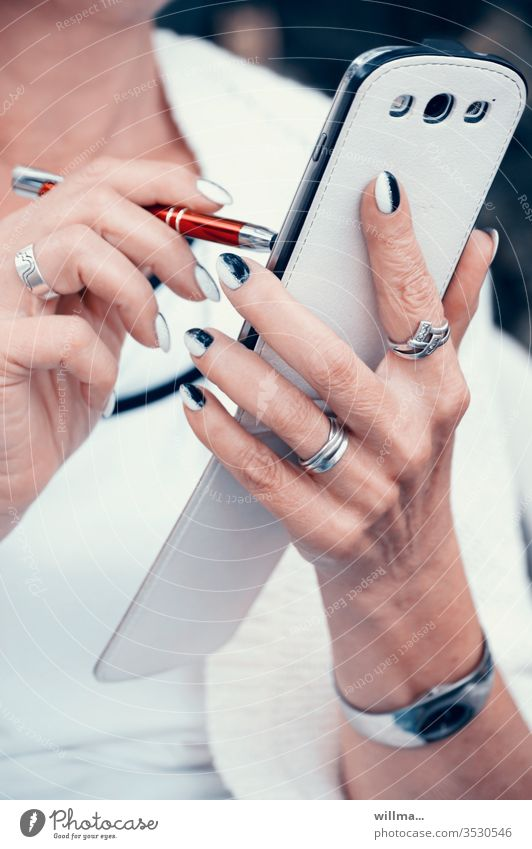 Woman with pen and smartphone in her hand and beautifully styled fingernails stylus Touchpen hands manicured Smartphone pen Stylus Digital mobility Inform SMS
