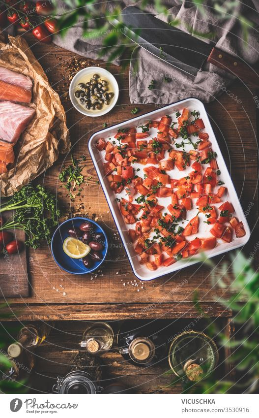 Cooking in a vintage kitchen.  Tomatoes on a baking sheet, raw fish , herbs and seasonings, olives oil , cleaver on a rustic wooden table background. Top view. Mediterranean food concept