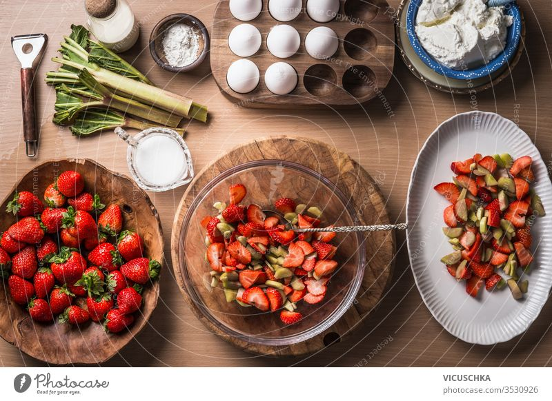 Fresh strawberries and rhubarb on wooden table background with ingredients for tasty seasonal cooking or baking. Top view. Healthy clean food. Paleo dieting. Home cuisine. Garden fruits eating