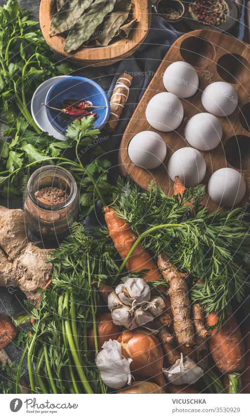 Various ingredients for tasty paleo diet. Healthy natural organic food concept. Carrots, onions, eggs, ginger roots vegetables, seasonings on dark rustic kitchen table background , top view.