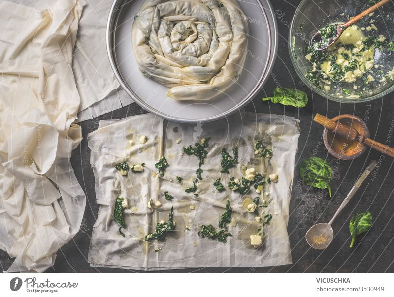 Backing preparation of savory pie with phyllo dough sheets stuffed with spinach and feta cheese . Top view. Balkan or oriental cuisine. Home cooking. Börek