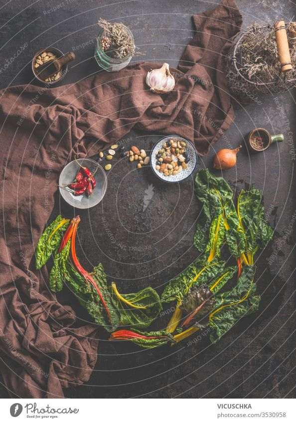 Food background with fresh colorful chard leaves on dark rustic table  background. Home cuisine. food herbs spices top view circle frame country style clean