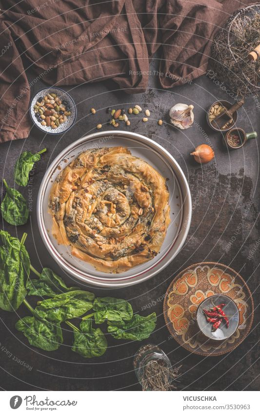 Tasty stuffed savory pastry pie with phyllo dough in traditional baking pan. Balkan or oriental cuisine. Börek tasty dark rustic background ingredients top view