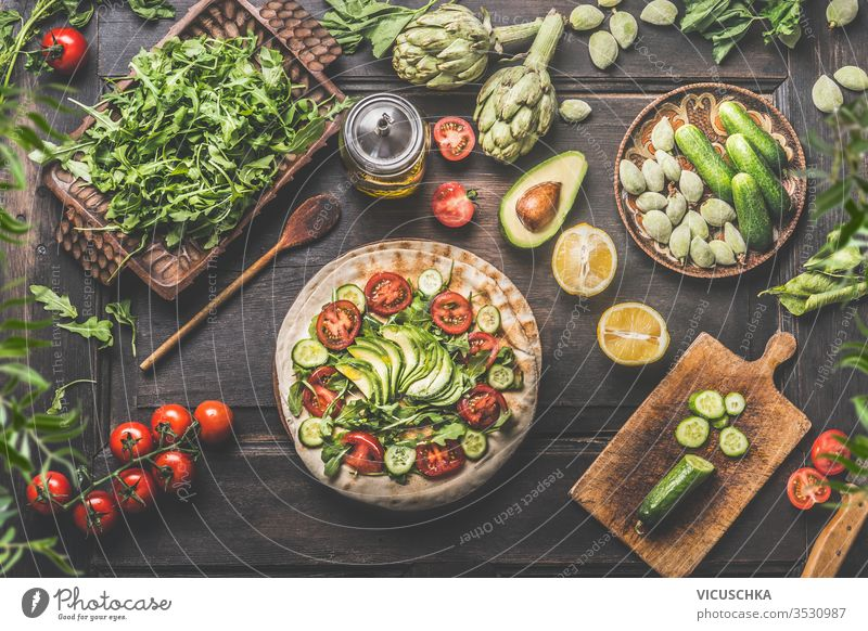 Healthy vegetarian lunch ingredients. Tortilla wraps with fresh vegetables, avocado , olives oil and lemon on rustic wooden kitchen table , top view. Cooking preparation. Vegan food.