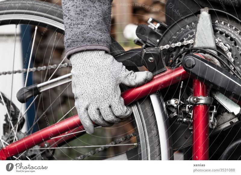 the gloved man's hand grabbed the bicycle after the repair at the frame and turned it around with power and momentum Bicycle Hand Bicycle chain Bicycle frame