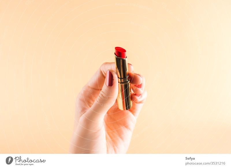 Female hand holding red lipstick on light orange glamour beauty female fashion color woman beautiful makeup closeup accessory nails personal girl fingers object