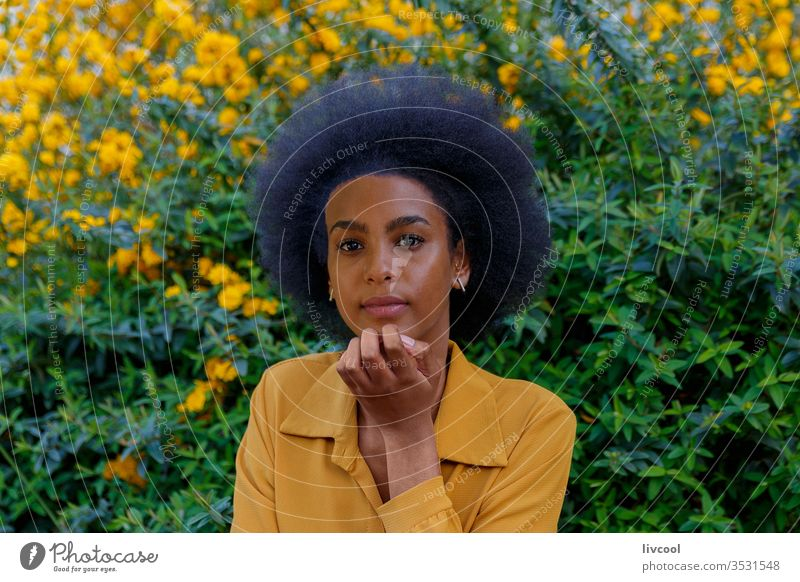 young woman with afro hair in a garden of yellow flowers black woman girl people portrait lifestyle cool lovely outdoor exterior nature afro-american beauty