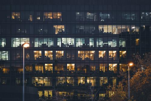 Illuminated windows of an office building at night lights illuminated rows frontal wide streetlamps color exterior outdoor outdoors city urban architecture