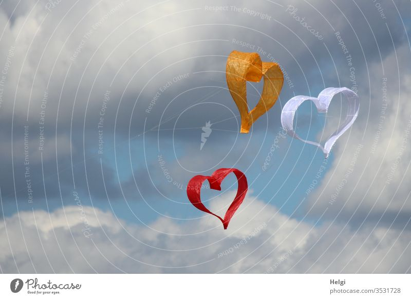 Dreiklang | three paper kites in the shape of hearts flying in the wind in front of a blue-grey sky Heart Paper Flying Sky Clouds Love Colour photo Deserted Day
