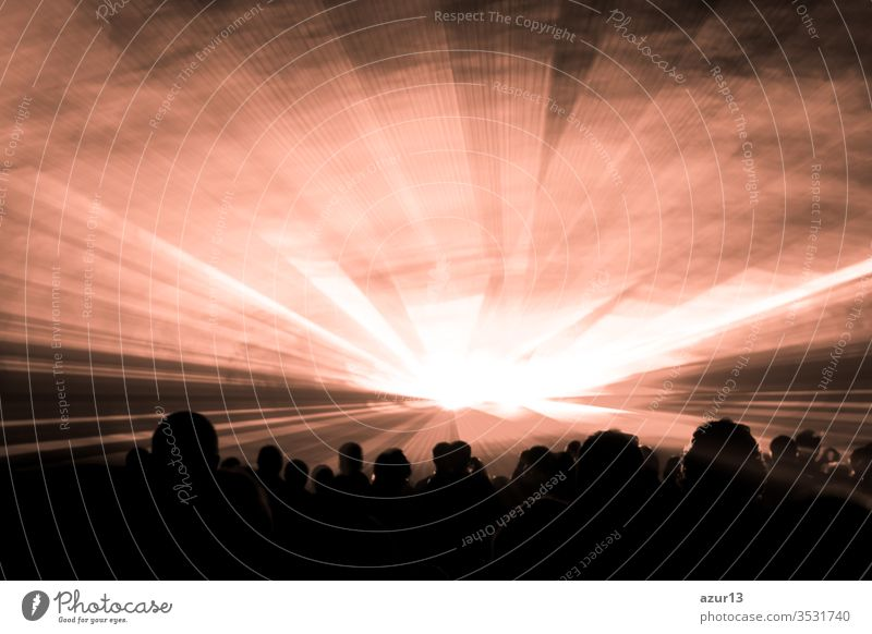 Bronze laser show nightlife club stage with party people crowd. Luxury entertainment with audience silhouettes in nightclub event, festival or New Years Eve. Beams and rays shining colorful lights