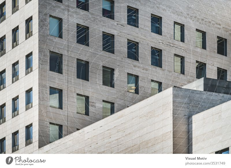 Geometric view of a modern business building built in roman travertine marble facade geometric windows rows glass perspective color outdoor exterior office