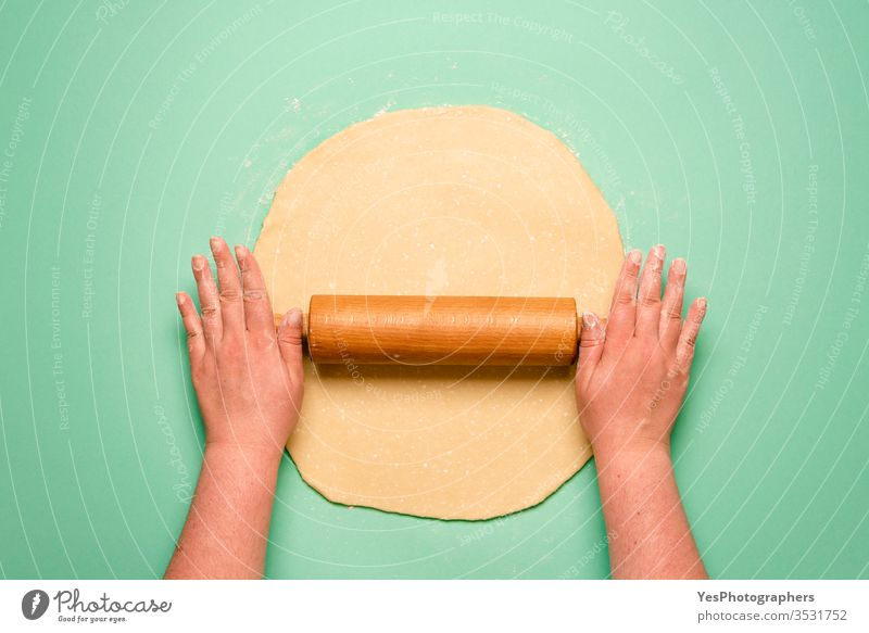 Making a pie top view. Woman stretching the dough on green table above view baker bakery baking cake cook crust cuisine culinary dessert domestic