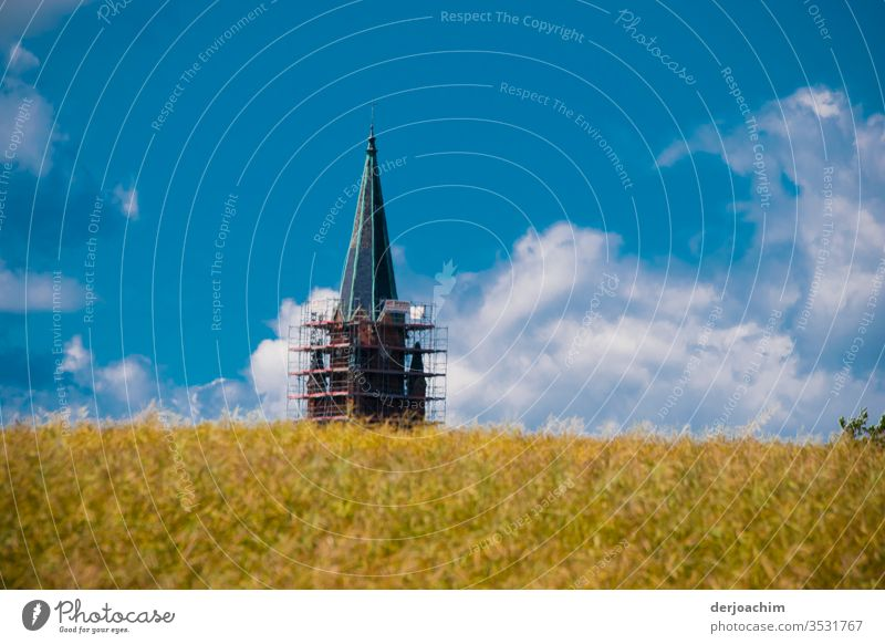 """ My destination "" Cornfield with church tower.  Behind a field. The church tower has a scaffolding at the bottom. Blue sky and clouds. Field Sky Clouds Sun"