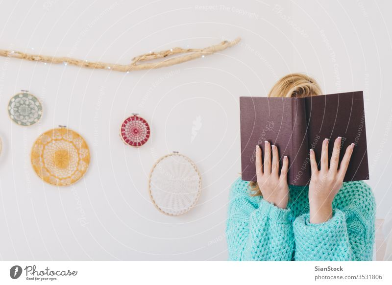 Young woman sitting in bed while reading a book girl coffee sweaters white beautiful morning home bedroom blonde wall lights dreamcatcher sunday young relax
