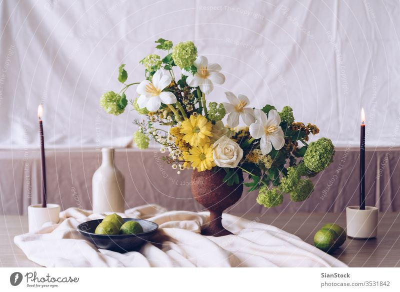 Still life with a beautiful bouquet of flowers, candles and limes table vase wedding decoration white background interior arrangement dinner romantic pink rose