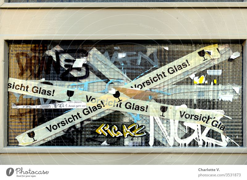 "Caution Glass | a broken window pane is held together with ""Caution Glass Tape"" and additionally embellished by graffiti. Pane Precuation Graffiti Trashy"