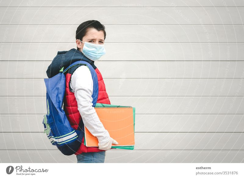 covid-19,portrait of a kid with medical mask and backpack going to school coronavirus child epidemic student pandemic quarantine back to school city schoolboy