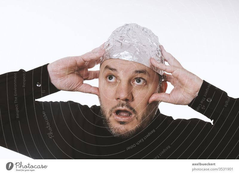 paranoid man wearing tin foil hat conspiracy theory aluminium mind control paranoia tinfoil cap helmet protection telepathy hum 5G scared shield strange