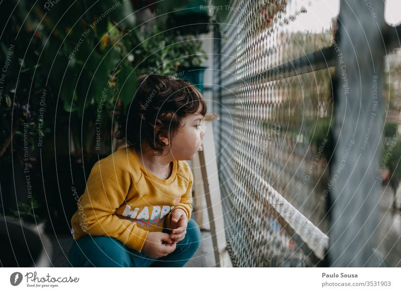 Child in the balcony childhood at home Lifestyle Autumn Authentic fall Balcony balcony rail Balcony planting green lockdown Green stay at home Exterior shot