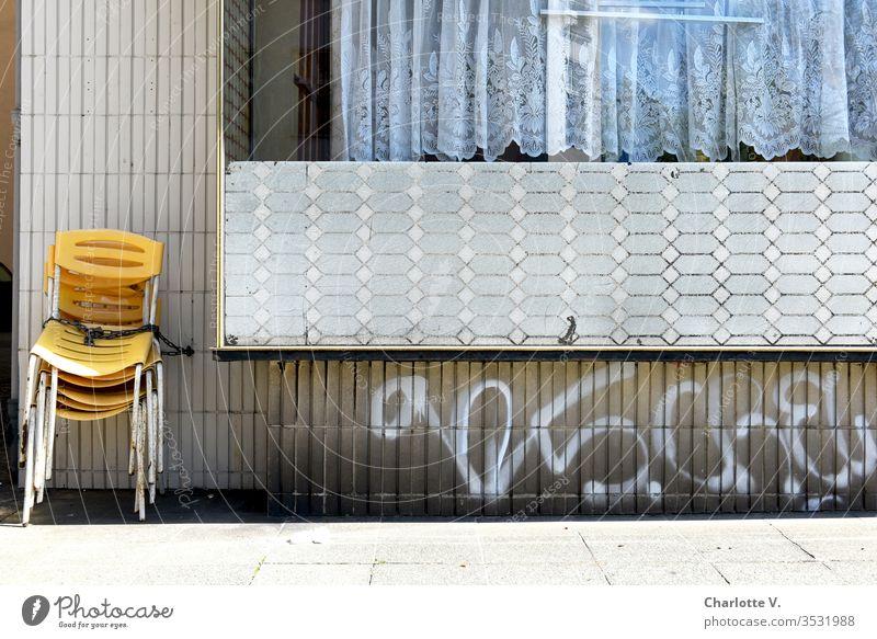 corona thoughts  Yellow chairs chained to a fifties retro wall are waiting to be used. The coronavirus corona crisis coronavirus SARS-CoV-2 tiles Graffiti leap