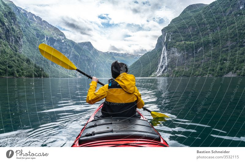 Woman paddling in Geirangerfjord, Norway Mountain Landscape Fjord Environment Colour photo Waterfall Beautiful weather Sunlight Clouds Exterior shot Deserted