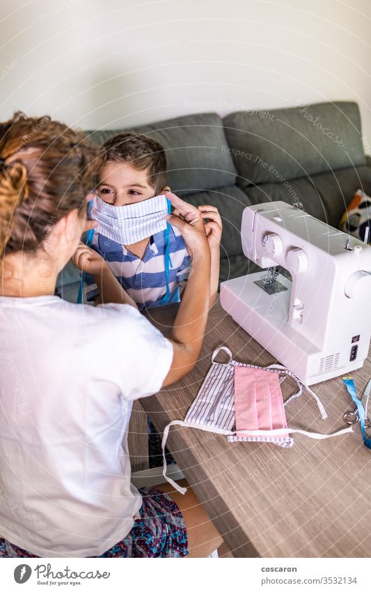 Mother putting a homemade face mask to her son adult boy business children clothes clothing corona coronavirus covid creative design domestic dress dressmaker