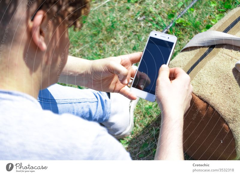 Man using a mobile phone sitting on the grass with a sports bag screen reflection device back detail zoom texting chatting lying lean relax break data