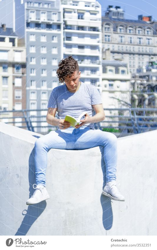Man with a modern hairstyle sitting on a white wall reading a book vertical city urban seat park street sunny sunbath summer relax holiday stylish fashion man