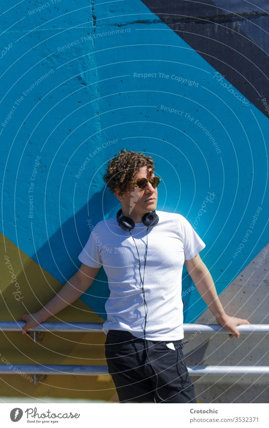 Portrait of a man with curly hair, sunglasses and a helmet on his neck leaning against a colored wall vertical portrait urbanite city modern fashion railing