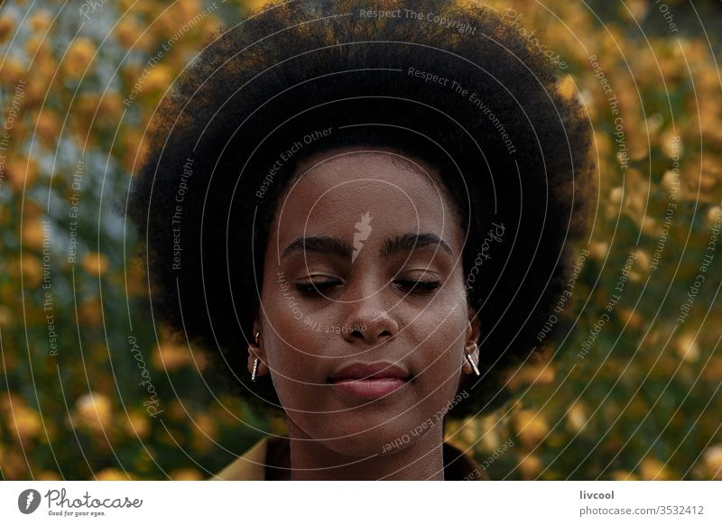 thoughtful afro woman with closed eyes in a garden black woman girl dreamer young people portrait lifestyle cool lovely yellow flower outdoor exterior nature