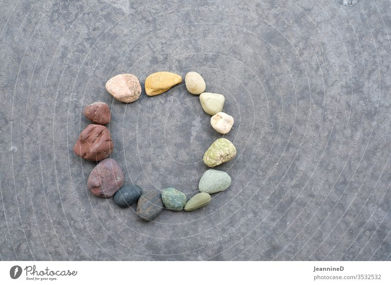 Coloured stones in a circle Circle circulation Nature Yoga Round Cardiovascular system Transience Harmonious grey background symbolic Future centred Patient