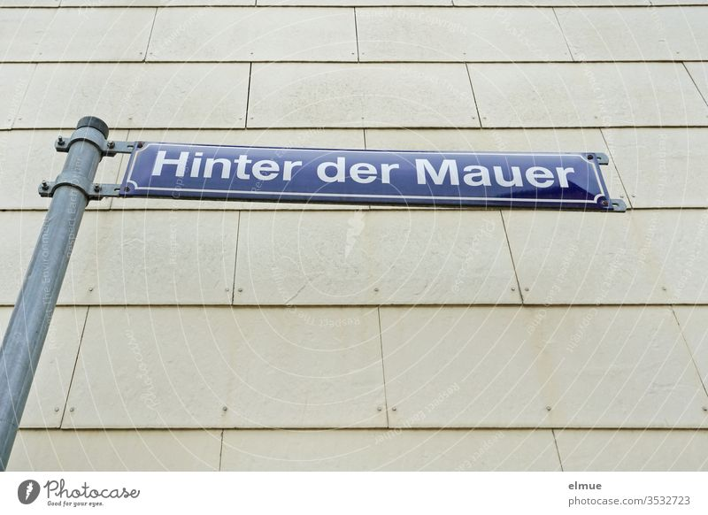 "blue street sign ""Hinter der Mauer"" in front of a grey facade behind the wall Facade street name Blue Gray Clue signage Wall (building) Signs and labeling"