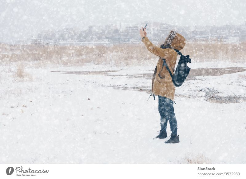 woman is taking photo in snowy landscape winter walking phone selfie takes smartphone mpbile cold outdoor step white nature fashion scene park girl beautiful