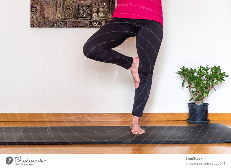 Middle aged woman practicing yoga, Tree pose. bending beauty workout european exercising flexibility wellness living single retired floor pink meditating