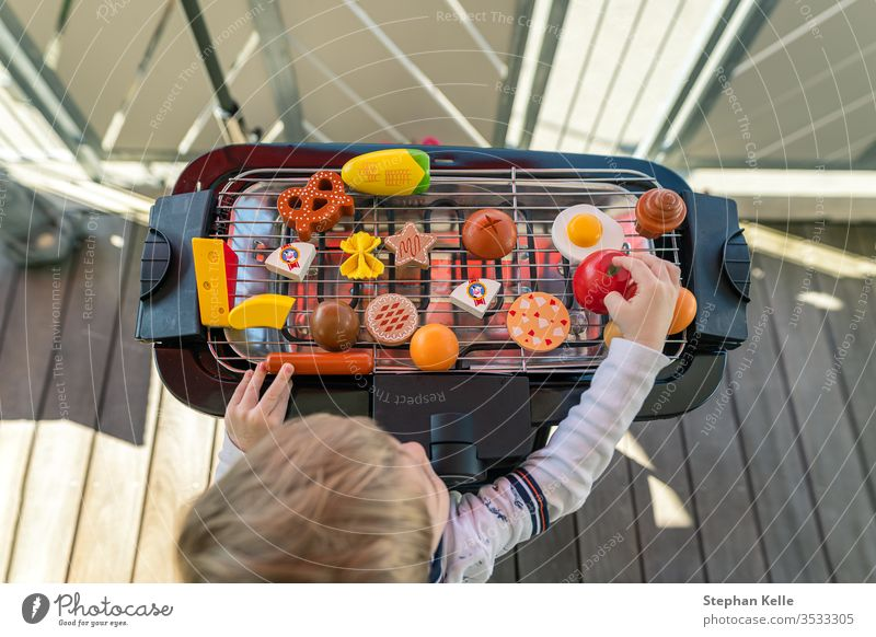 A little boy starts grilling by playing with his vegetables and sausage food toys at the balcony. He is creating a delicious meal for his family. barbecue bbq