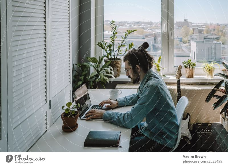 Young man with beard sitting on the chair and using laptop. Freelance work from home in quarantine concept video chat online shopping using technology