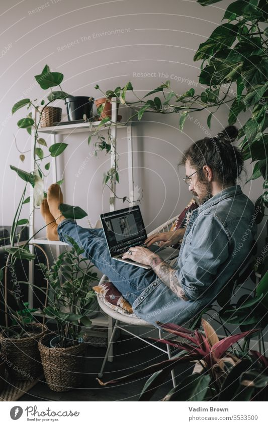 Young man with beard sitting on the chair and using laptop. Freelance work from home in quarantine concept apartment attractive browsing plants chatting