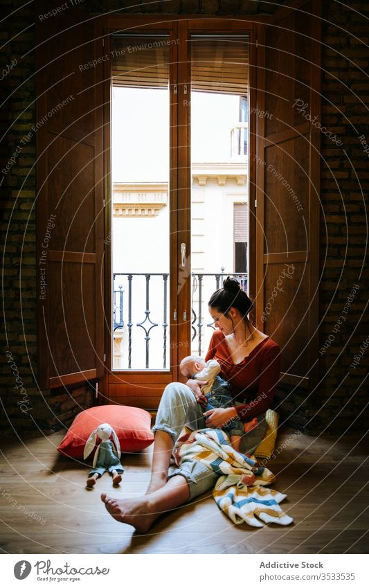 Happy mother breastfeeding baby near window home happy love rest cozy sit woman cute room hug embrace smile child kid childhood little care together parent