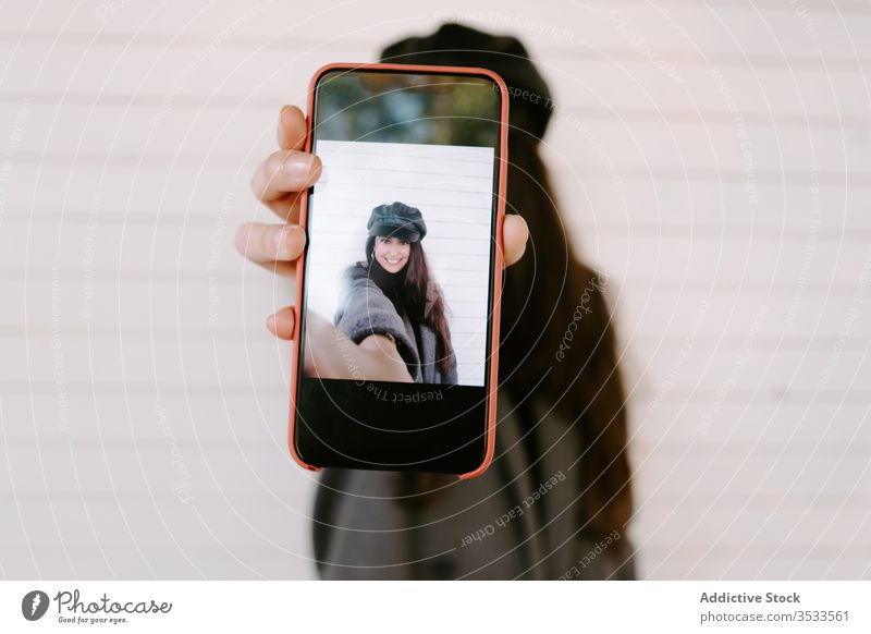 Young female showing smartphone with selfie woman wall street city urban modern young building photo mobile social media share demonstrate gadget device lady
